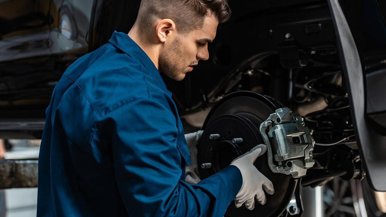 So kontrolieren sie ihren Bremsen verschleiß - Mechaniker repariert die Bremsscheiben
