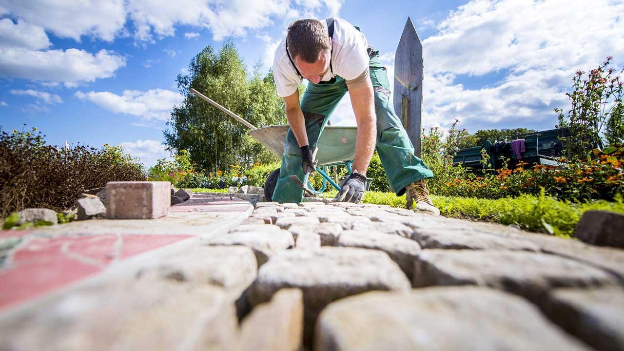 Tipps zum Pflastern einer Steinterrasse - Handwerker bei der Arbeit