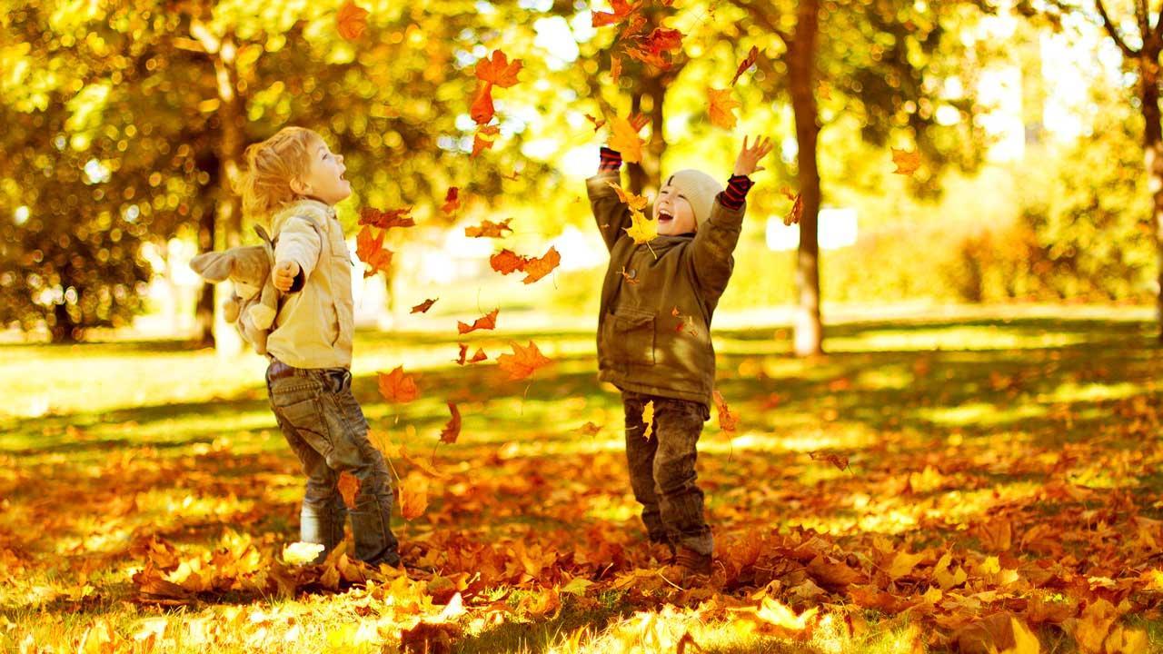 Spielideen für den Herbst, sowohl Indoor als auch Outdoor - Kinder spielen im Laub