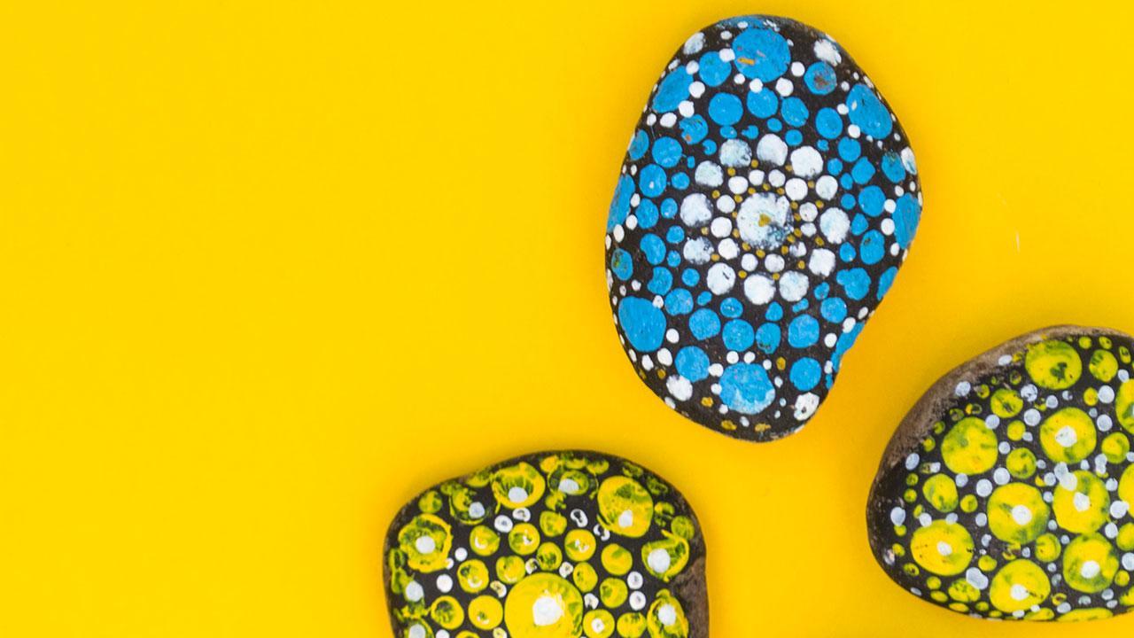 Steine bemalen und auslegen - blaue und gelbe Muster