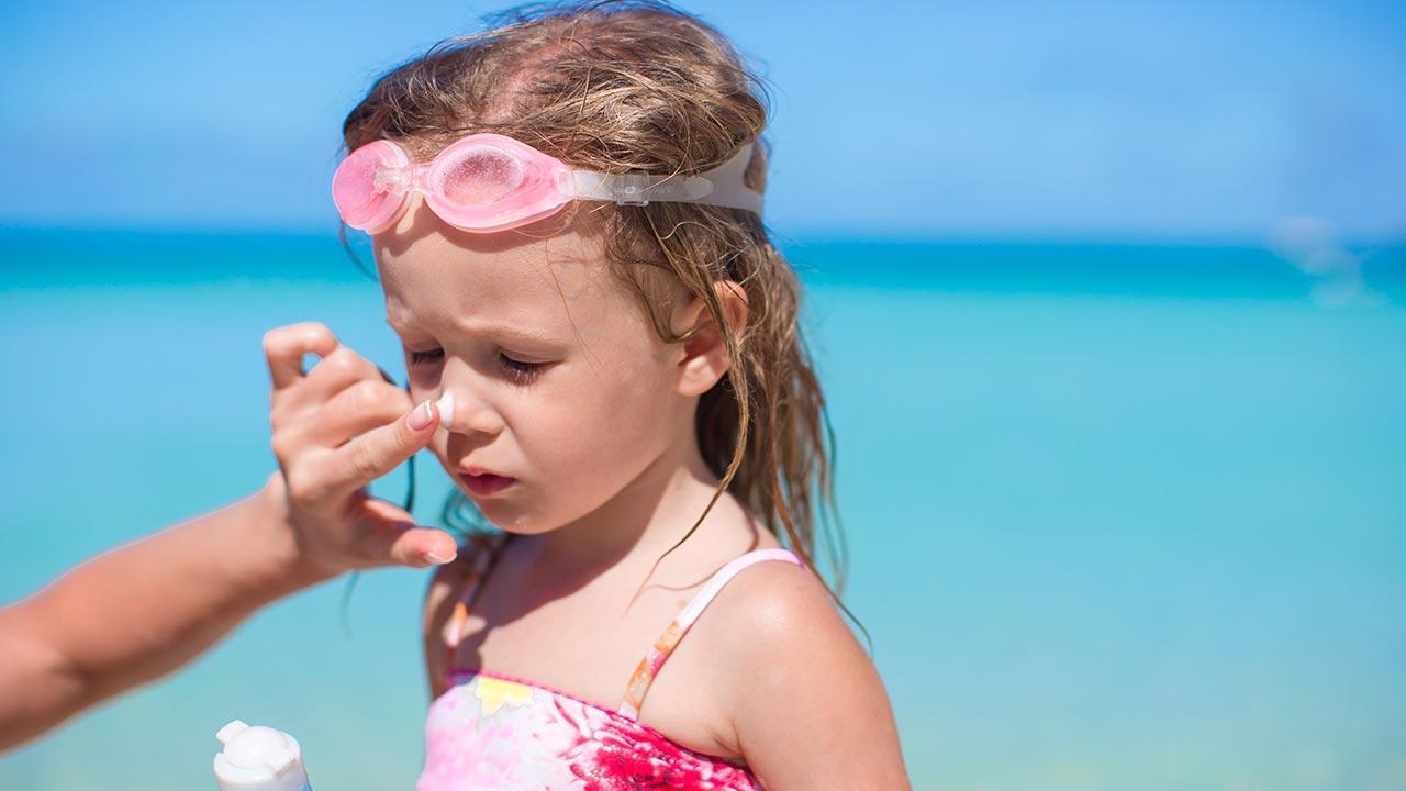 Sonnenmilch oder Sonnenöl - Kind Sonnencreme auf der Nase