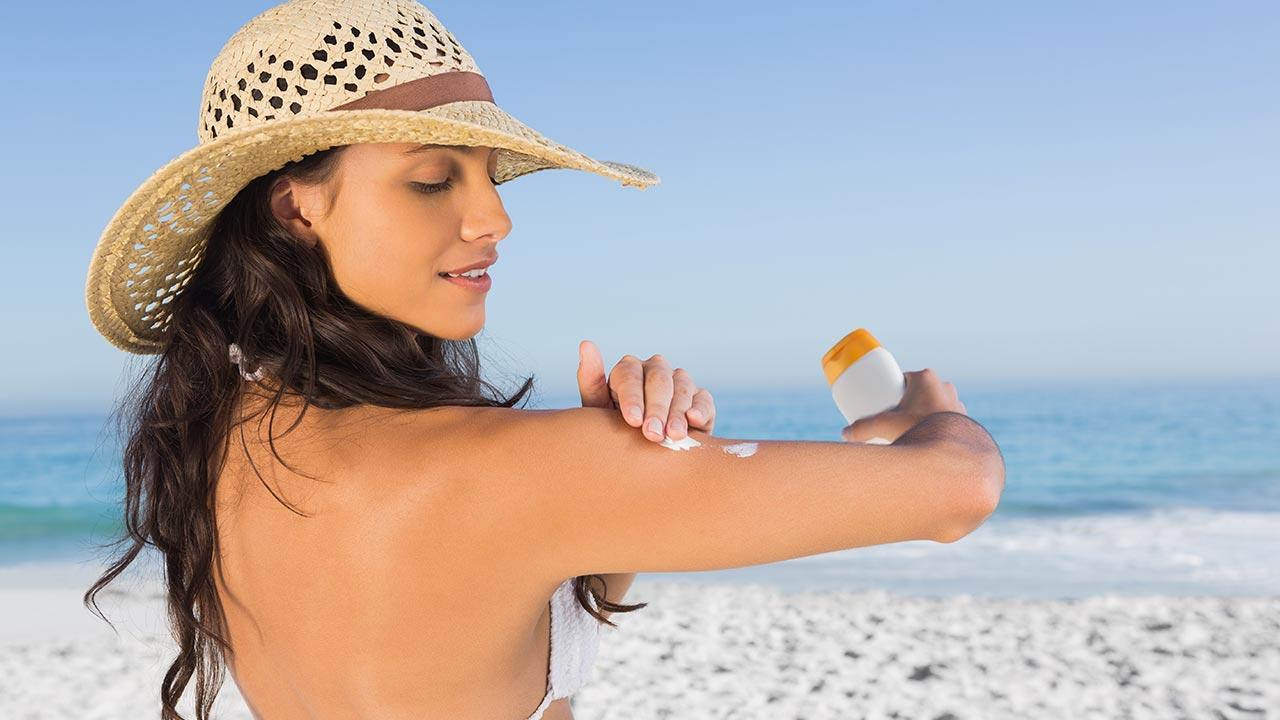 Sonnenmilch oder Sonnenöl - Frau mit Sonnenhot nutzt Sonnencreme