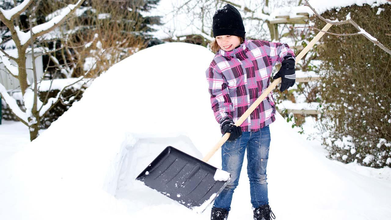 Iglu im Garten selbst bauen - Mädchen mit Schneeschaufel