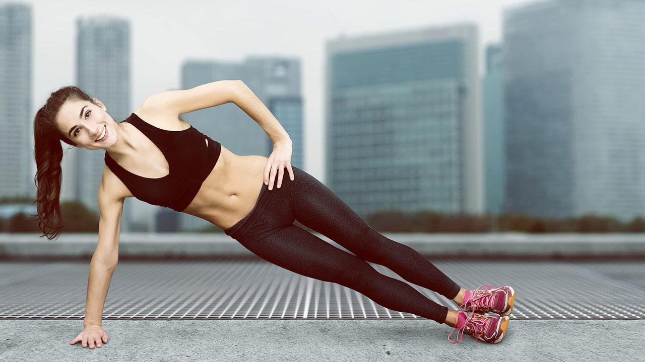 Freeletics pro und contra - junge Frau macht Übungen am Dach