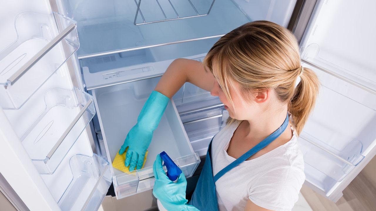 Frühjahrsputz im Kühlschrank - blonde Frau