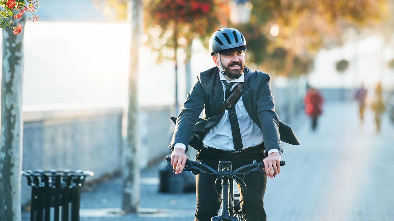 Mit dem E-Bike in den Frühling starten - Mann im Anzug im Sonnenschein