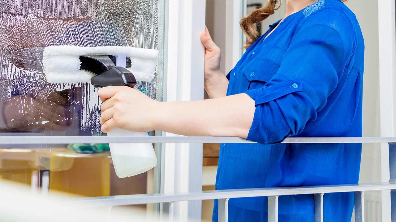 Fenster einfacher putzen mit Fenstersauger - Frau im blauen Arbeitsmantel