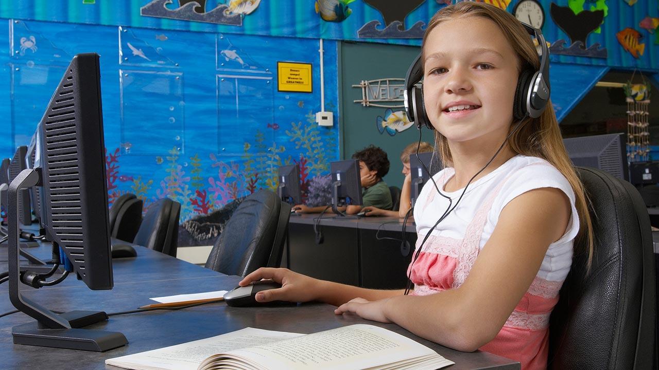 Der optimale Schreibtischstuhl für mein Kind - Mädchen mit Kopfhörer am Computer