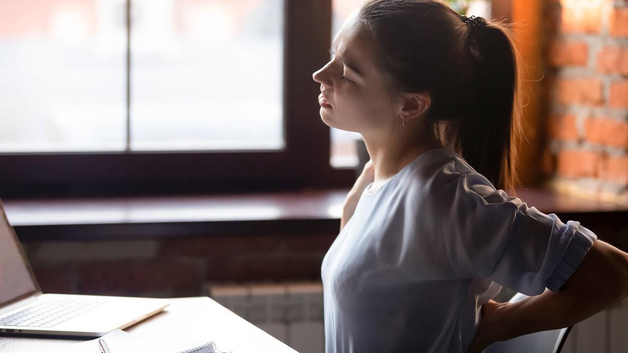 Tipps gegen Rückenschmerzen - der richtige Arbeitsplatz - Frau mit Rückenschmerzen
