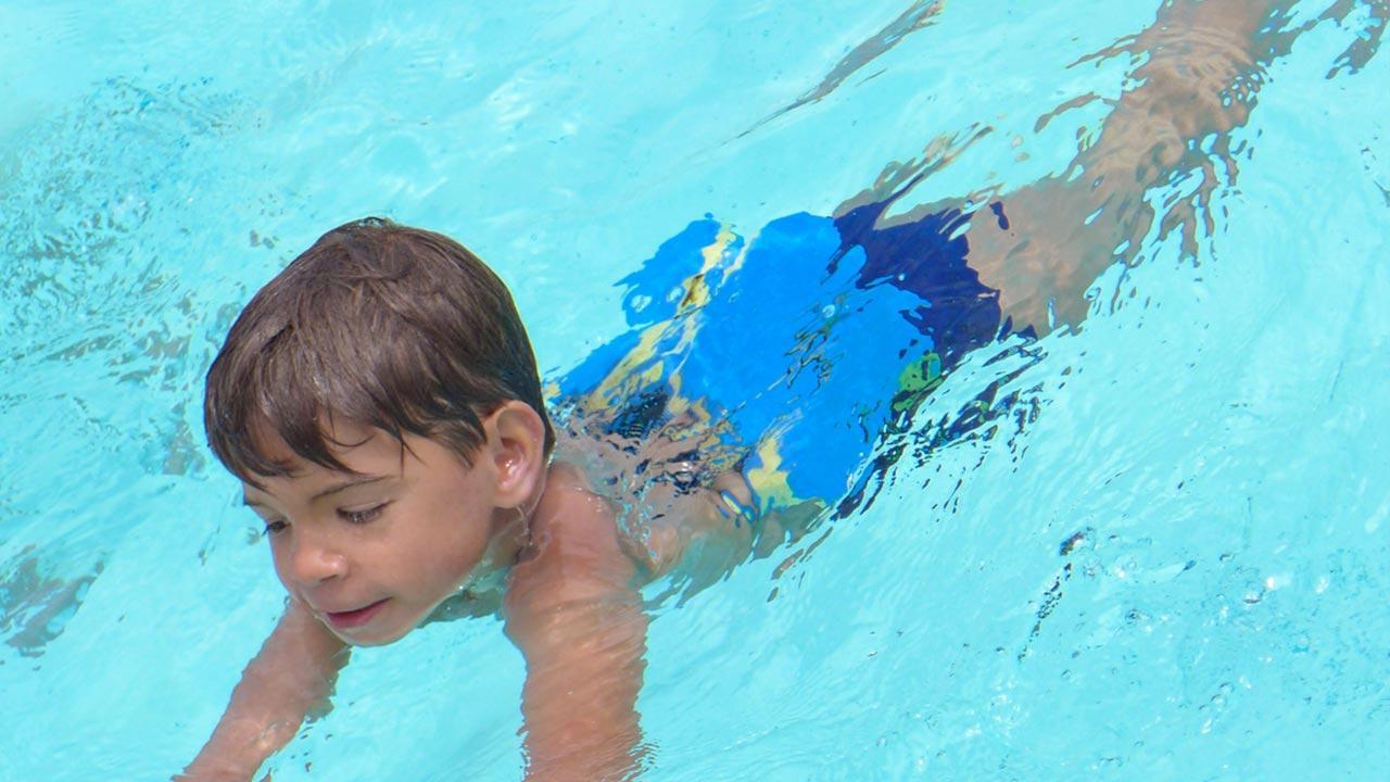 Die besten Schwimmhilfen für Kinder / kleiner Junge mit Schwimmgürtel