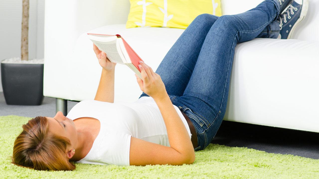 Tipps gegen Rückenschmerzen - Soforthilfe bei akuten Rückenschmerzen / Frau liegt am Boden mit den Beinen am Sofa