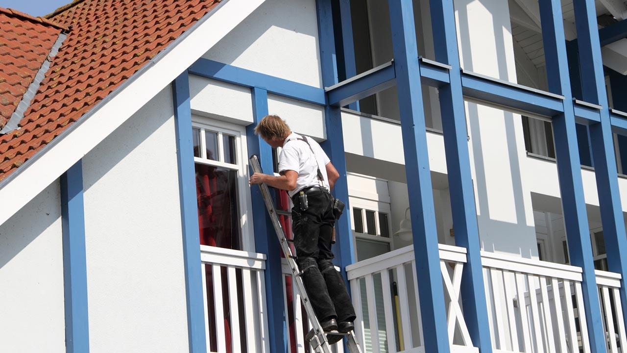 Fenster neu streichen - was ist zu beachten / Mann streicht den Fensterrahmen