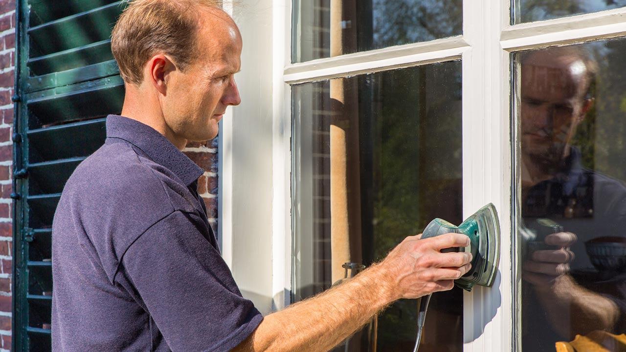 Fenster neu streichen - was ist zu beachten / Mann schleift den Fensterrahmen
