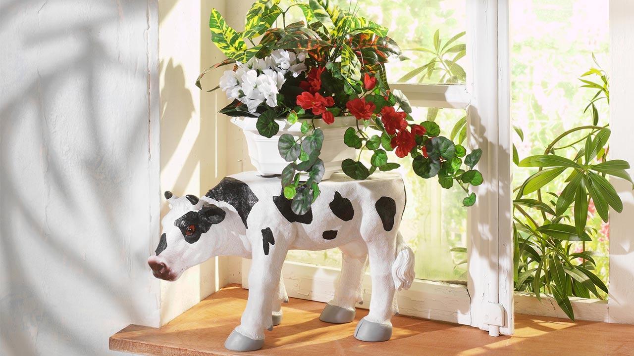 Schöne Sommerdeko auf dem Fensterbrett / eine Kuh mit Blumen