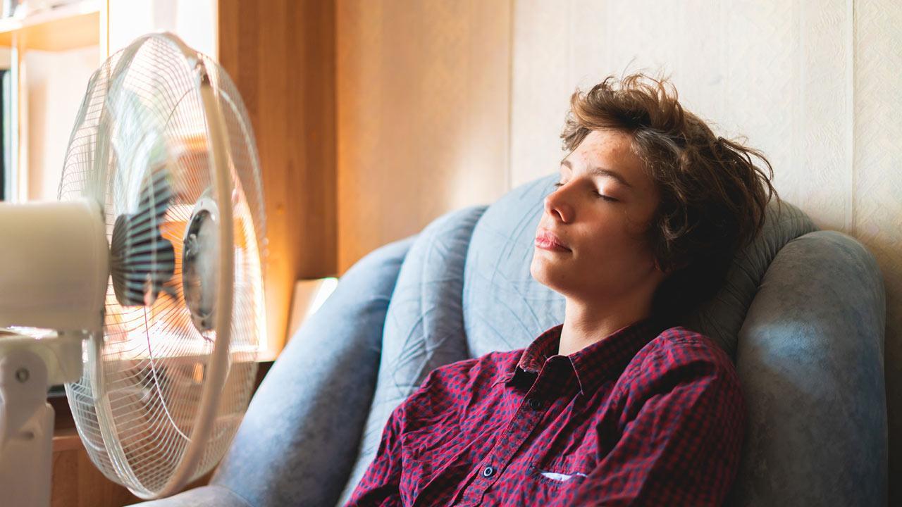 Tipps für guten Schlaf trotz Sommerhitze / Junge genießt den kühlen Wind des Ventilators