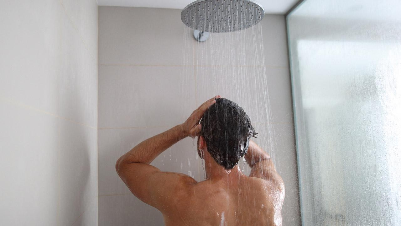 Tipps für guten Schlaf trotz Sommerhitze / Mann duscht kalt