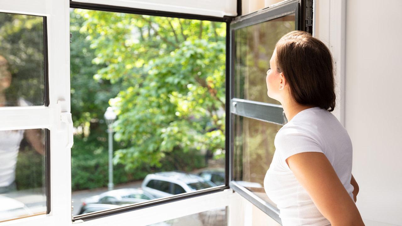 Wie schütze ich mich vor der Sommerhitze ? / Frau öffnet das Fenster
