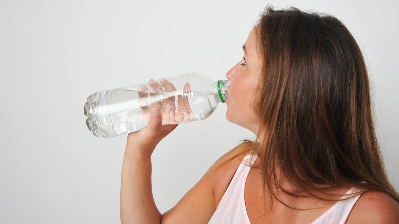 Wie schütze ich mich vor der Sommerhitze ? / Frau trinkt Wasser