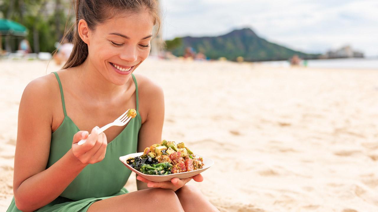 Poke - Fischsalat aus Hawaii / eine Frau isst eine Poke