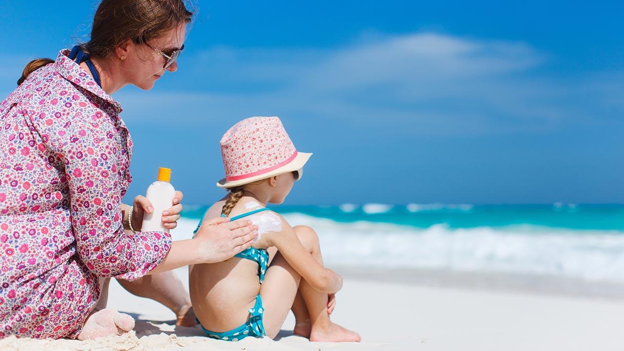 Der passende Sonnenschutz für mein Kind / eine Frau schmiert ihrer Tochter den Rücken ein