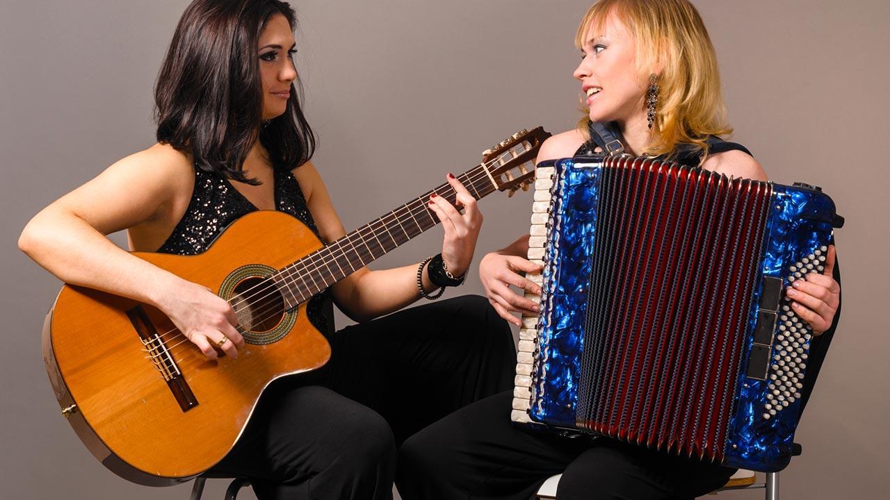 Akkordeon spielen - So legen Sie los / zwei Frauen machen Musik mit einer Gitarre und einem Akkordeon