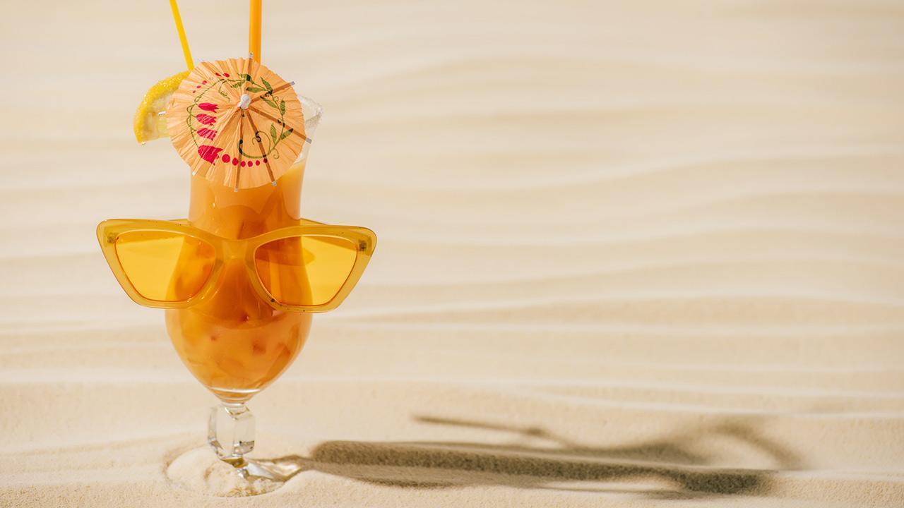 Planters Punch - Unser Longdrink-Tipp im September / ein Planters Puntch mit Sonnenbrille und Schirmchen