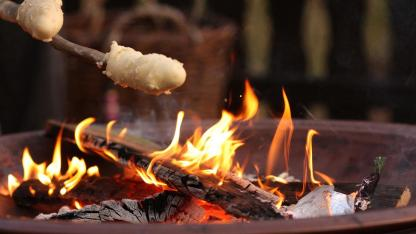 Stockbrot am Lagerfeuer mit Kindern / Nahaufnahme von einem Stockbrot über dem Feuer