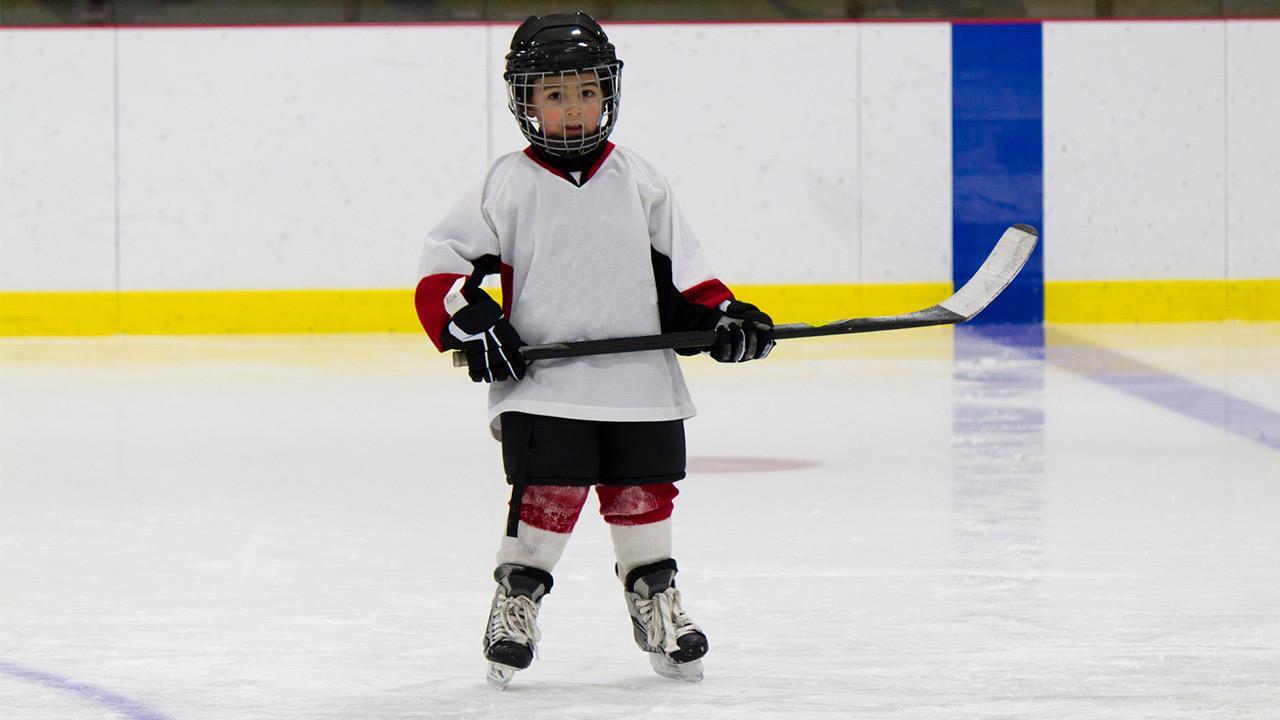 Schlittschuhe für Kinder - Das sollten sie beachten / kleiner Junge steht am Eis