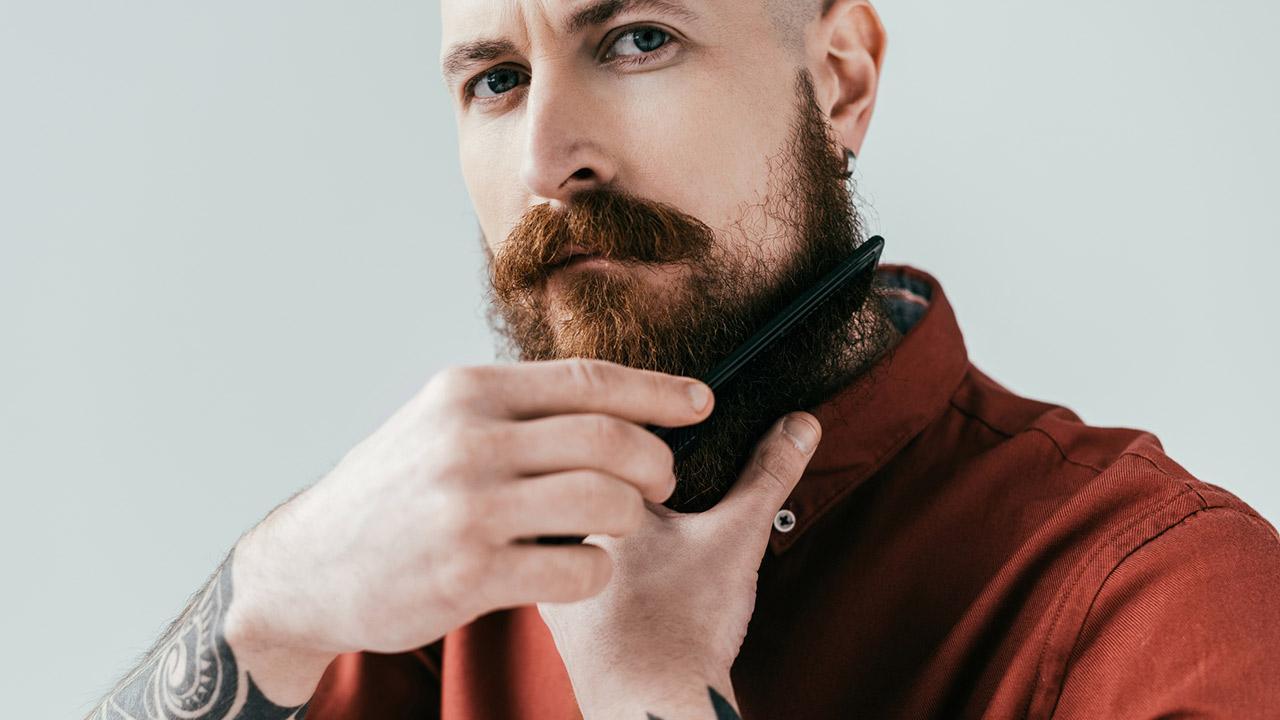 Die richtige Bartpflege im Winter - ein Mann kämmt seinen Bart