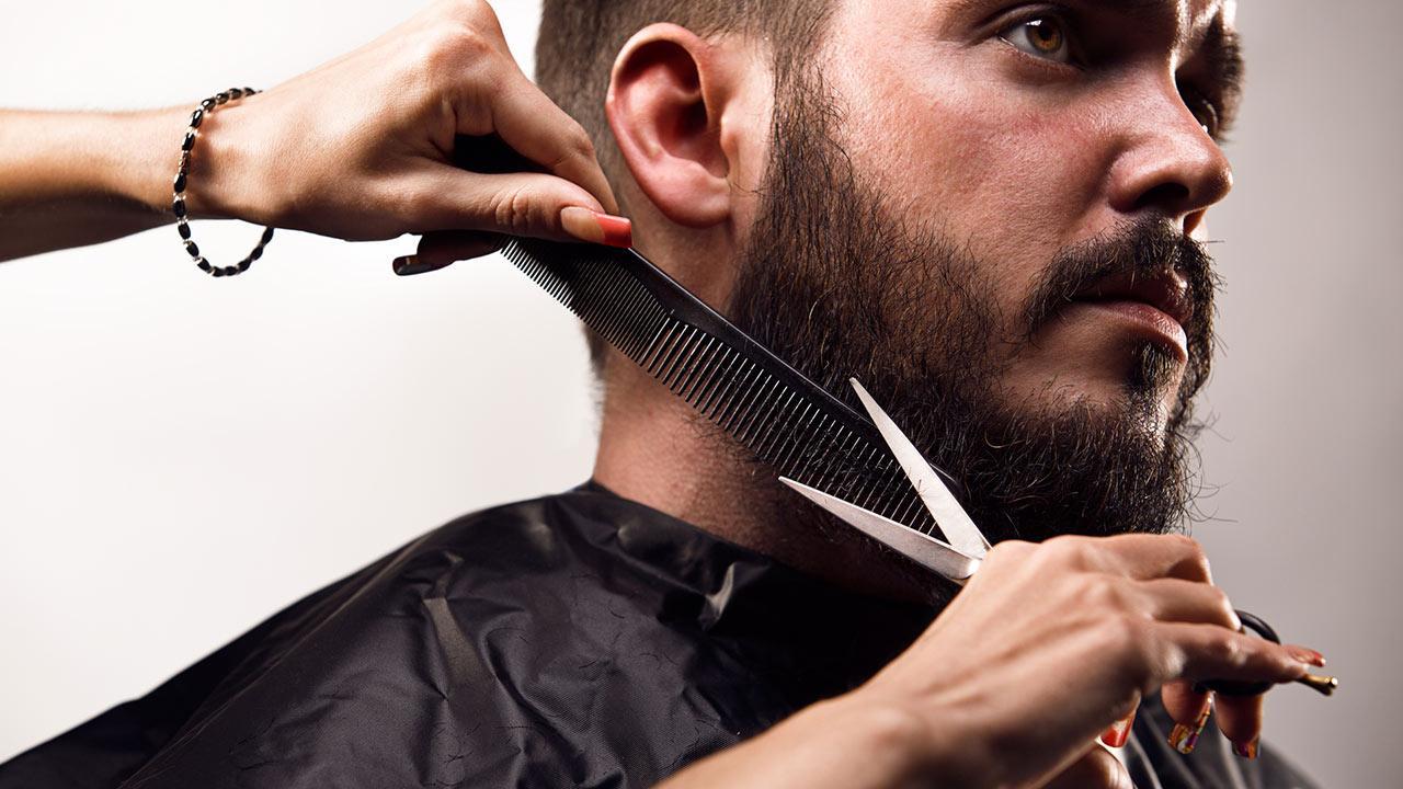Die richtige Bartpflege im Winter - ein Mann lässt seinen Bart kürzer schneiden