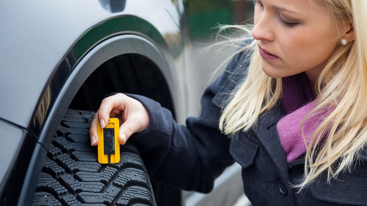 So prüfen sie ihre Sommerreifen - Frau misst Profiltiefe ihres Reifen